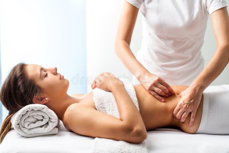 Terapeut som gör läka massage på den kvinnliga magen royaltyfria bilder