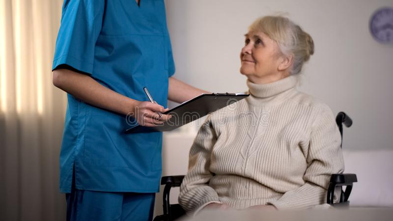 Terapeut som g?r anm?rkningar i damen f?r sjukdomshistorier och f?r unders?ka ?ldre, sjukhus royaltyfria foton