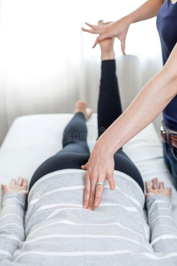 Terapeut som ger Kinesiologybehandling i ljust rum royaltyfria bilder