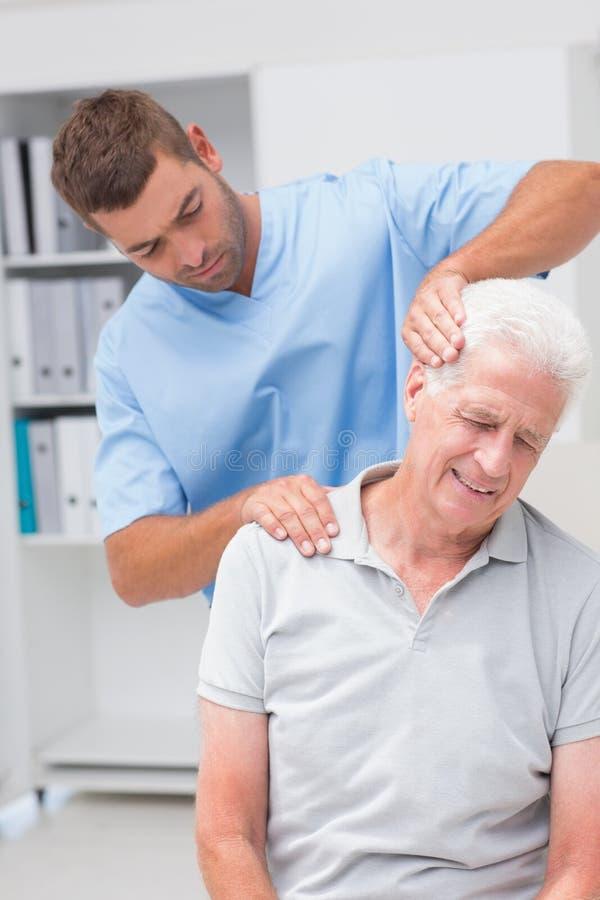 Terapeut som ger massage till den höga manliga patienten royaltyfria bilder