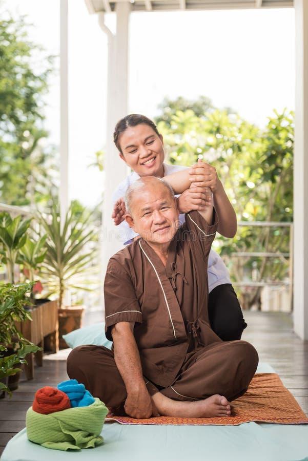 Terapeut som ger massage till den höga manliga patienten royaltyfri foto