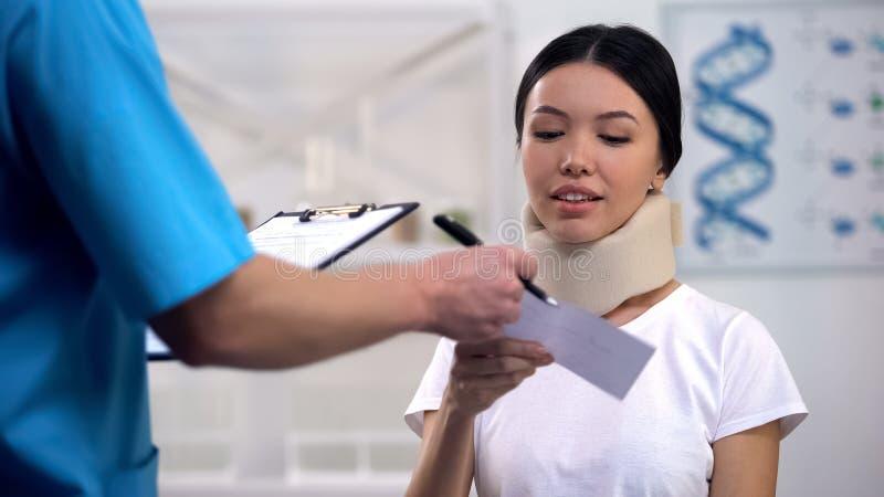Terapeut som ger räkningen till att le damen i den cervikala kragen för skum, sjukförsäkring royaltyfria bilder