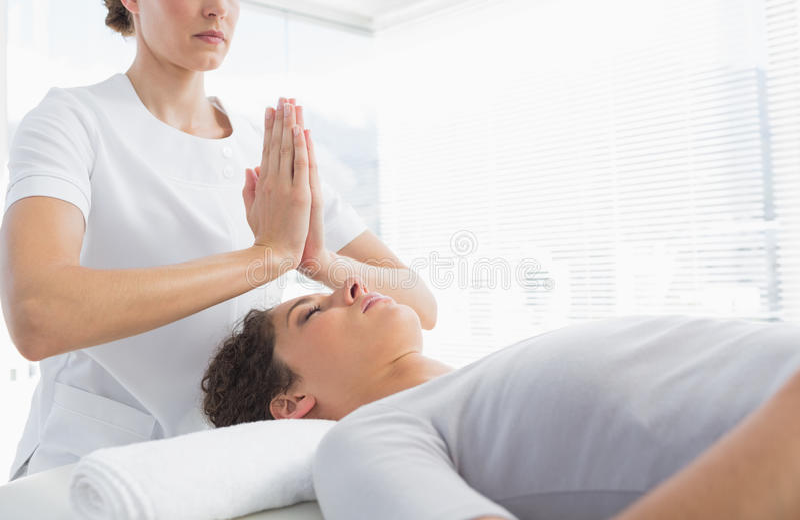 Terapeut som ger Reiki behandling till kvinnan royaltyfri foto