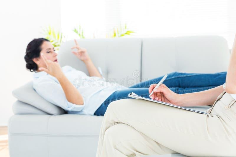Terapeut som lyssnar hennes patient och tar anmärkningar arkivfoton