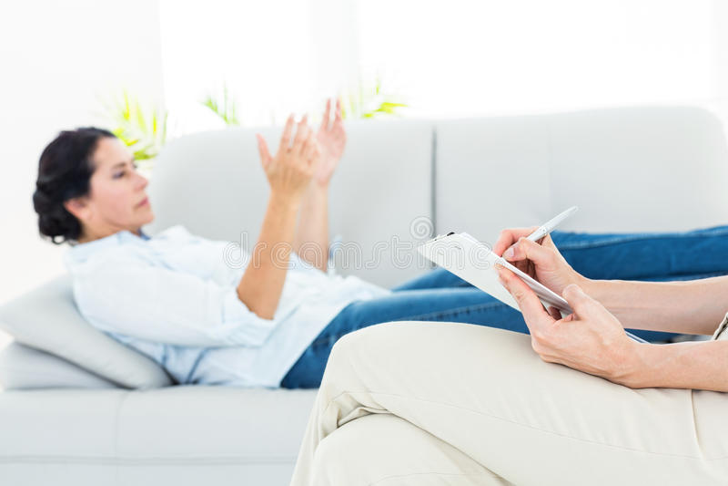 Terapeut som lyssnar hennes patient och tar anmärkningar royaltyfria bilder
