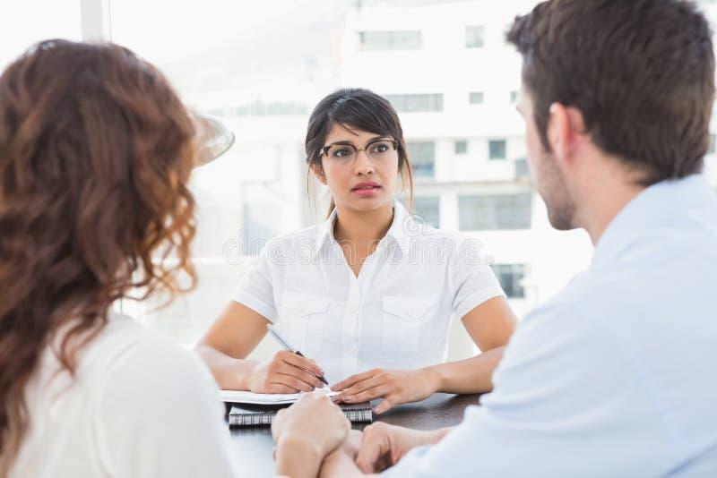 Terapeut som lyssnar hennes patienter och tar anmärkningar royaltyfri fotografi