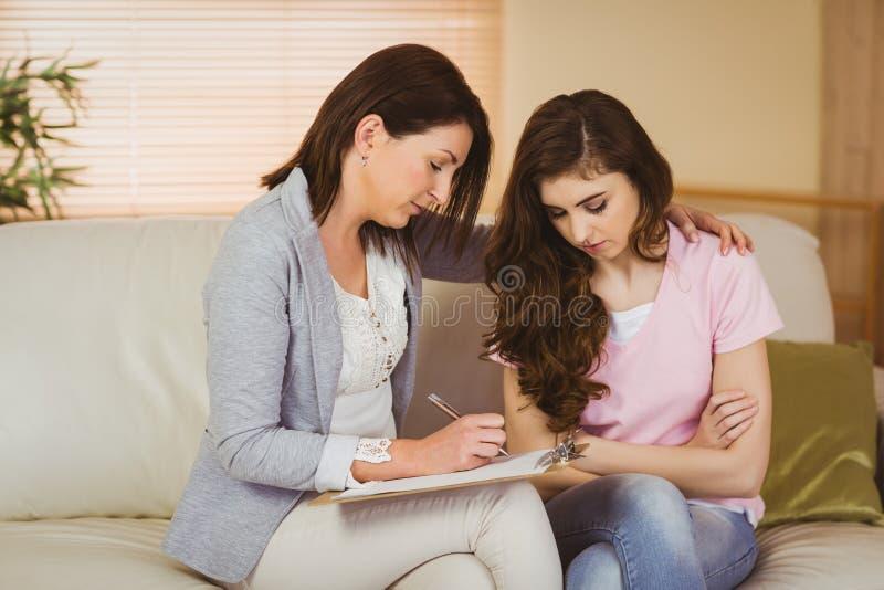 Terapeut som lyssnar till hennes upprivna patient royaltyfri bild