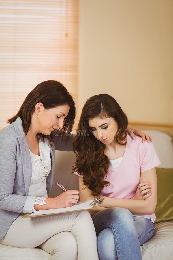 Terapeut som lyssnar till hennes upprivna patient arkivfoto