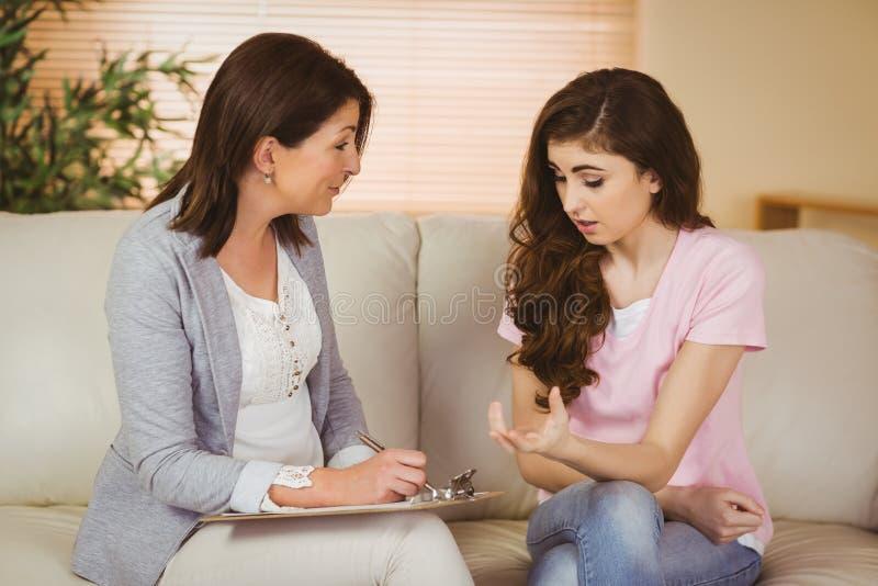 Terapeut som lyssnar till hennes upprivna patient arkivfoton