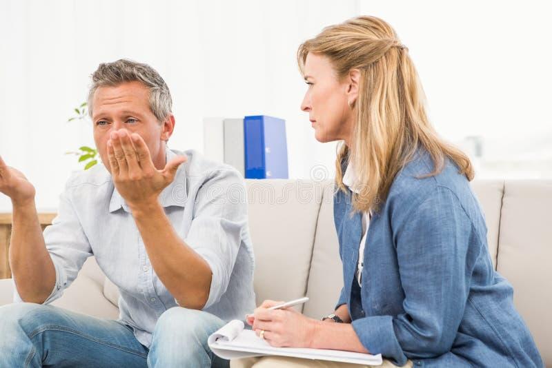 Terapeut som lyssnar till manliga patientbekymmer royaltyfri bild