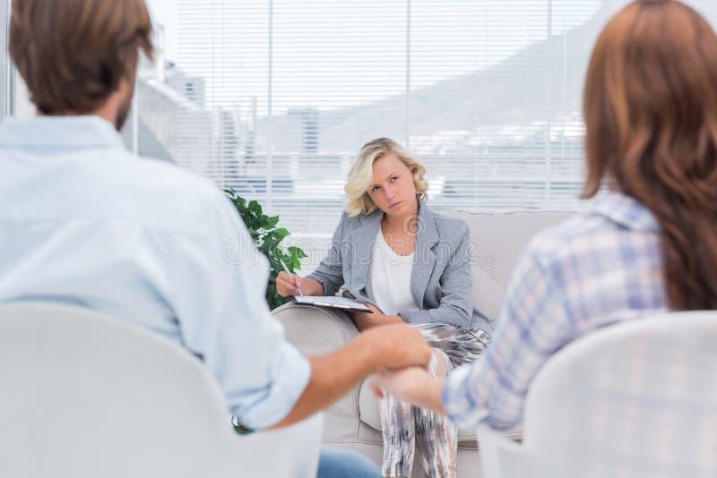 Terapeut som lyssnar till par under en period royaltyfri bild