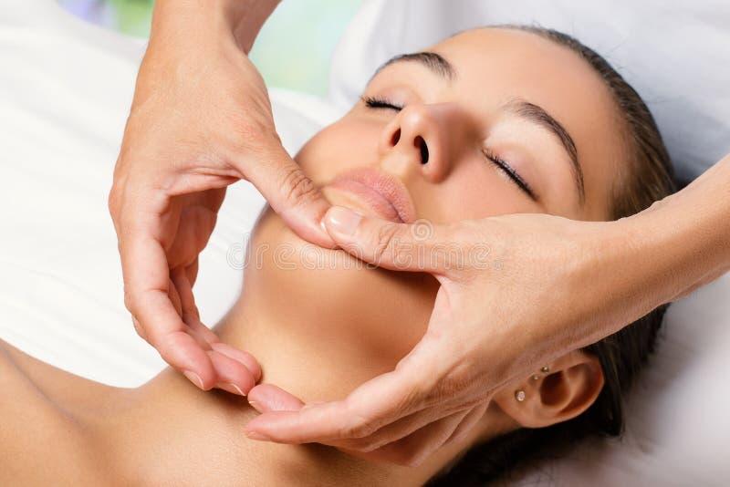 Terapeut som masserar den kvinnliga hakan royaltyfri fotografi