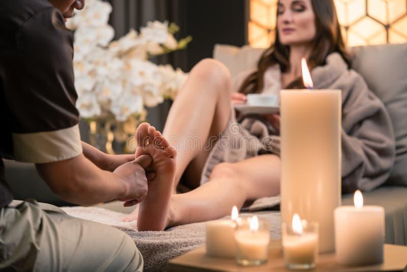 Terapeut som masserar foten av en kvinnlig klient i asiatisk skönhetmitt arkivfoton