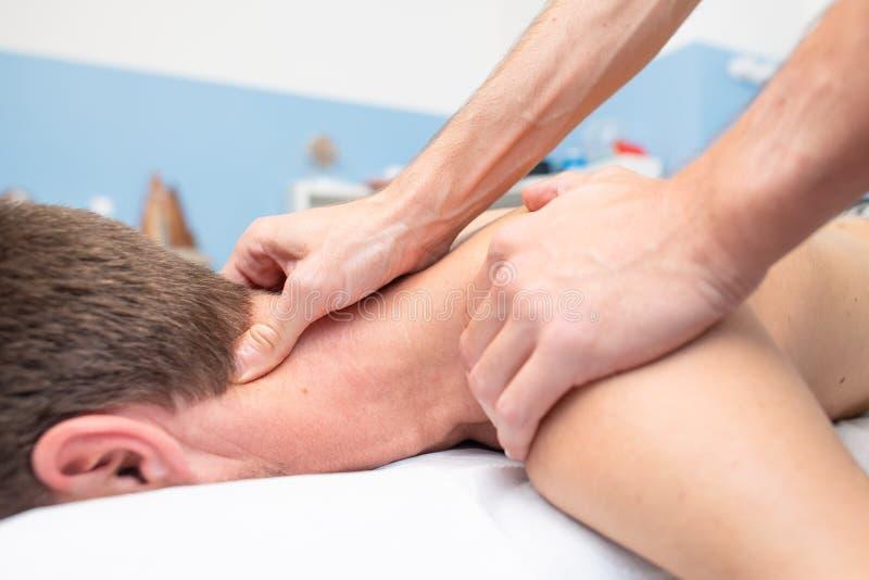 Terapeut som masserar halsen av den unga mannen royaltyfria foton