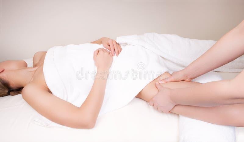 Terapeut som masserar kvinnas ben royaltyfria bilder