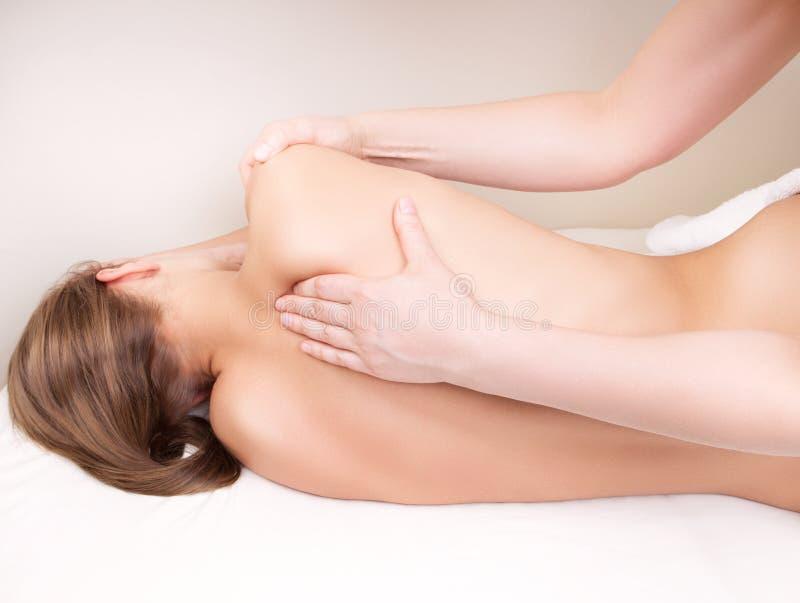 Terapeut som masserar kvinnas skulderblad arkivfoto
