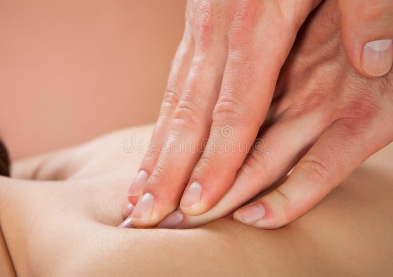 Terapeut som masserar kvinnliga kunds baksida på brunnsorten royaltyfri foto