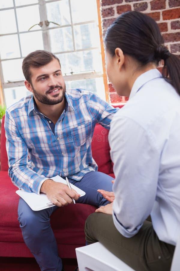 Terapeut som råder hans lyssnande patient royaltyfri bild