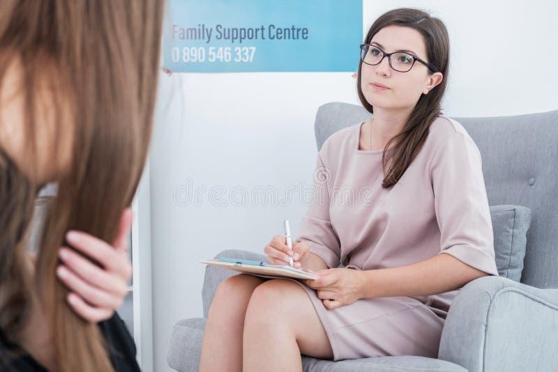 Terapeut som rymmer en penna och legitimationshandlingar och talar till hennes patient w arkivbilder