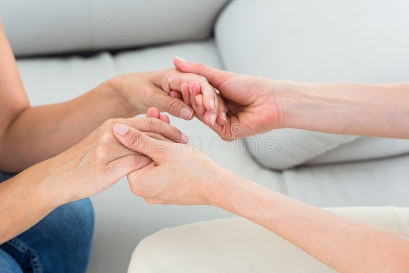 Terapeut som rymmer hennes patienthänder fotografering för bildbyråer