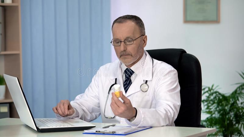 Terapeut som söker efter mediciner i online-katalog på bärbara datorn, prescribtion arkivfoton
