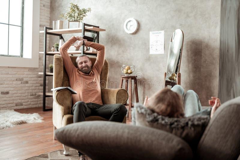 Terapeut som sträcker hans muskler efter lång tröttsam terapi royaltyfria bilder