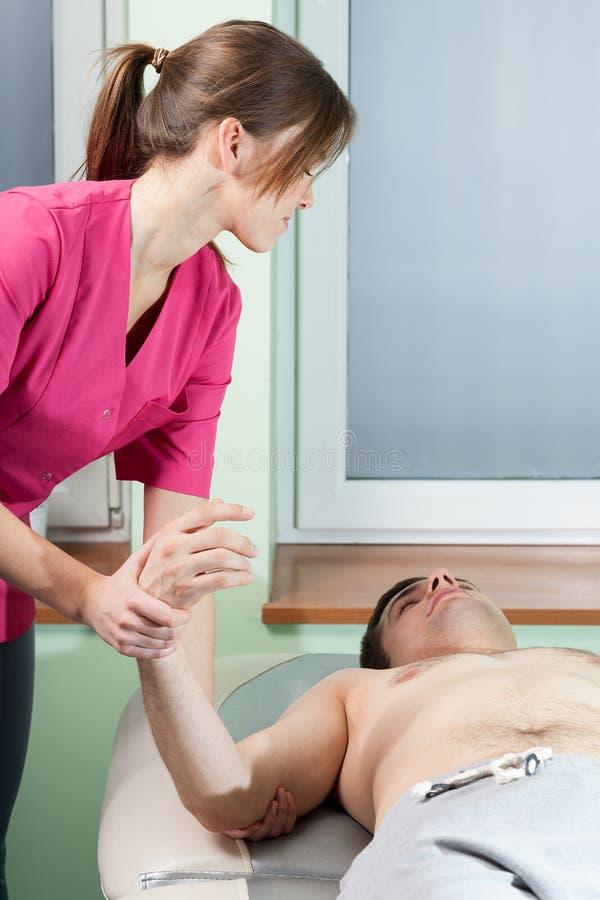 Terapeut som sträcker mans arm fotografering för bildbyråer