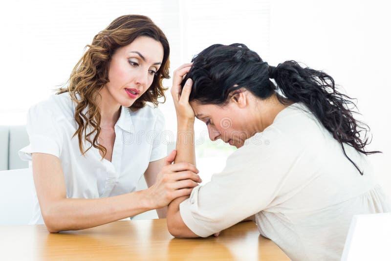 Terapeut som tröstar hennes patient arkivfoton