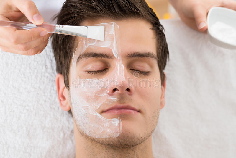 Terapeuta Applying Face Mask a equipar imagens de stock royalty free