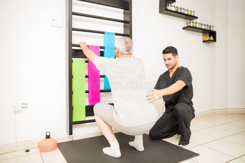 Terapeuta Assisting Mature Man que hace posiciones en cuclillas en clínica fotos de archivo libres de regalías