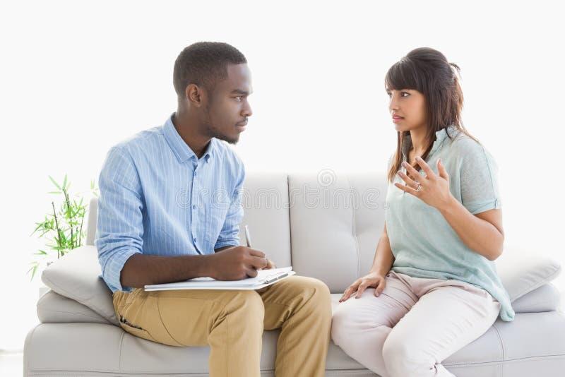 Terapeuta bierze notatki na jego pacjencie zdjęcie royalty free