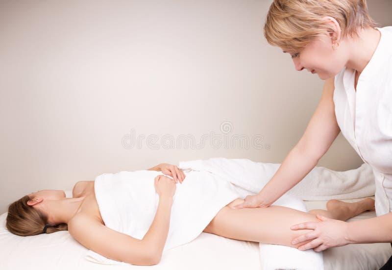 Terapeuta calificado que da masajes a la pierna de la mujer imágenes de archivo libres de regalías