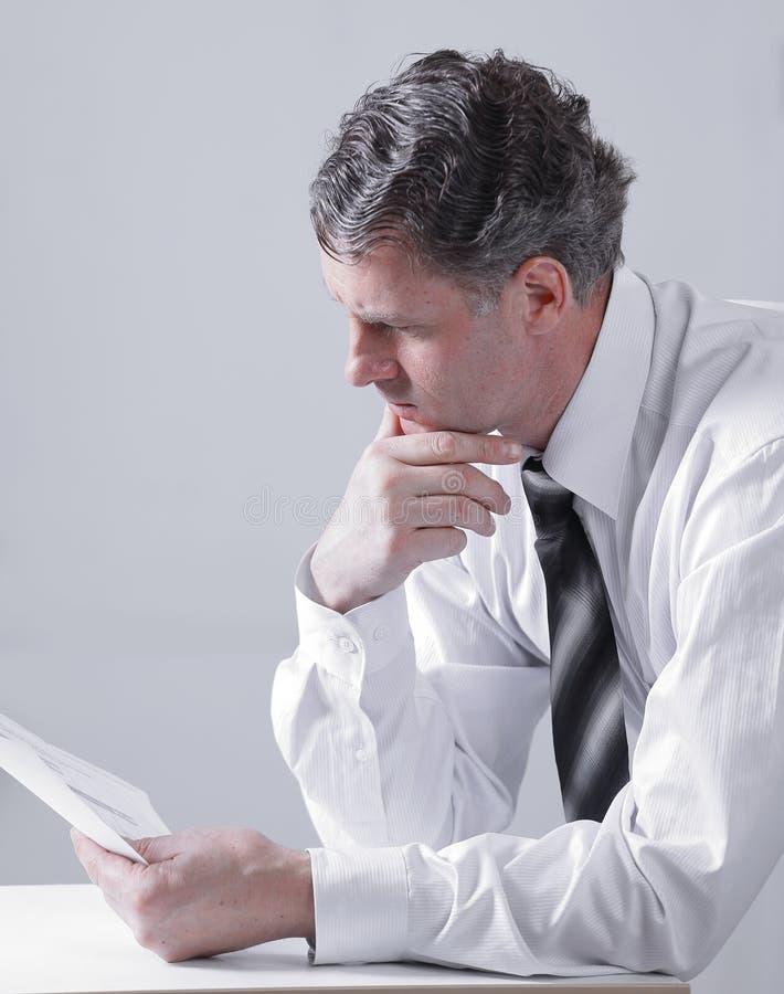 Terapeuta czyta cierpliwą ` s mapę, siedzi za biurkiem zdjęcie stock