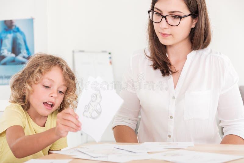 Terapeuta da educação da criança que usa suportes durante uma reunião com uma criança com problemas fotografia de stock royalty free