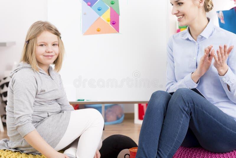 Terapeuta de discurso que sorri na menina foto de stock