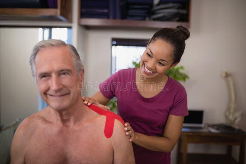 Terapeuta de sexo femenino sonriente que aplica la cinta terapéutica elástico en hombro del pati masculino mayor descamisado imagen de archivo libre de regalías