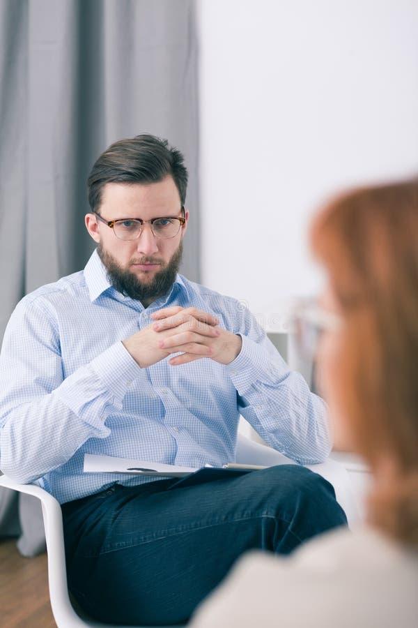 Terapeuta de sexo masculino que se sienta en una silla con las manos unidas y que escucha su paciente imagenes de archivo
