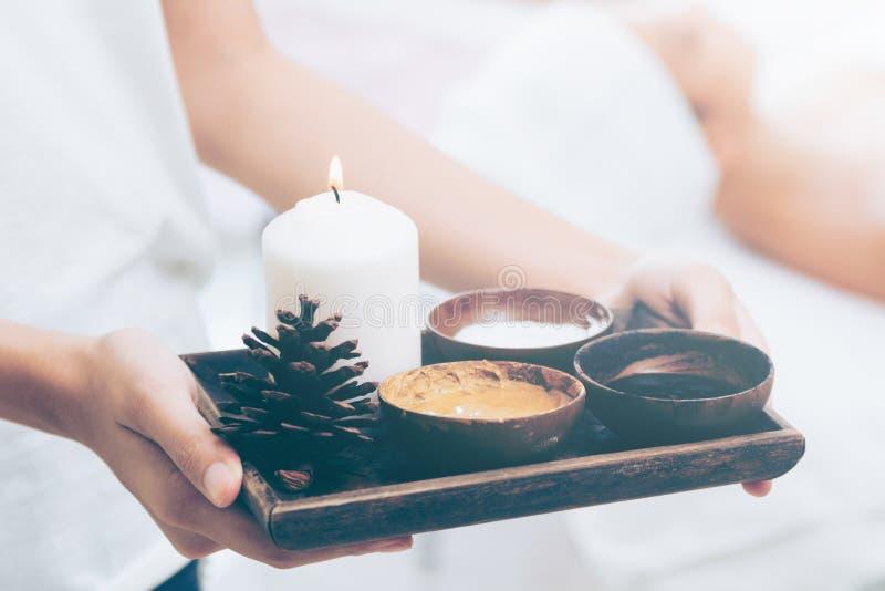 Terapeuta del masaje con el sistema caliente del tratamiento del balneario foto de archivo