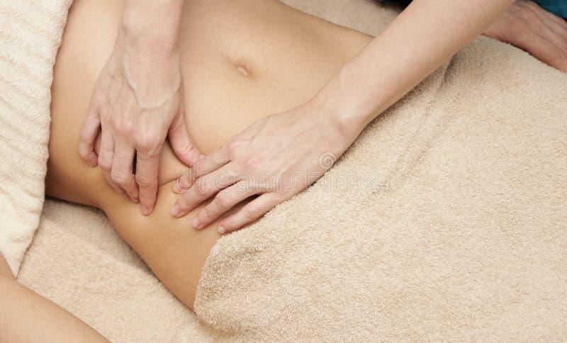 Terapeuta del masaje que hace el masaje terapéutico del abdomen para una mujer foto de archivo libre de regalías