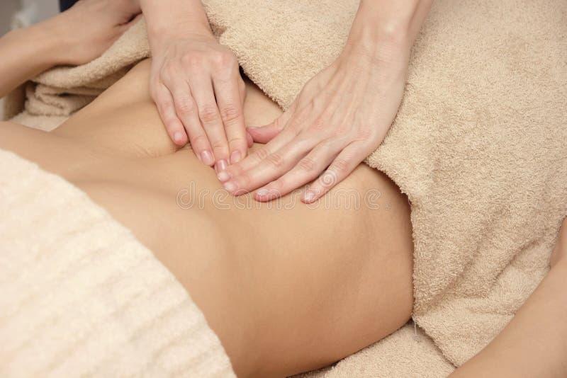 Terapeuta del masaje que hace el masaje terapéutico del abdomen para una mujer imagen de archivo libre de regalías
