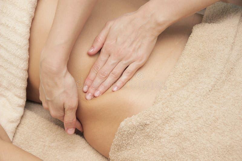 Terapeuta del masaje que hace un masaje térmico para el abdomen para una mujer foto de archivo