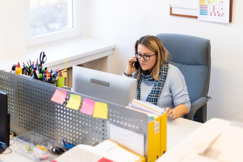 Terapeuta del ni?o femenino en una oficina durante una llamada de tel?fono, usando el calendario en l?nea para programar citas de fotos de archivo libres de regalías