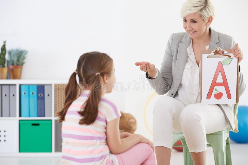 Terapeuta e criança de discurso imagem de stock royalty free
