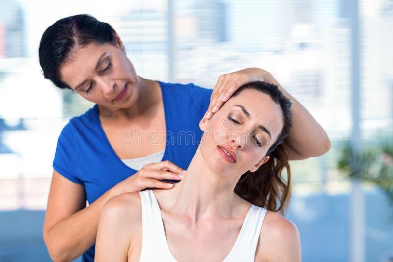 Terapeuta egzamininuje jej pacjent szyję zdjęcia stock