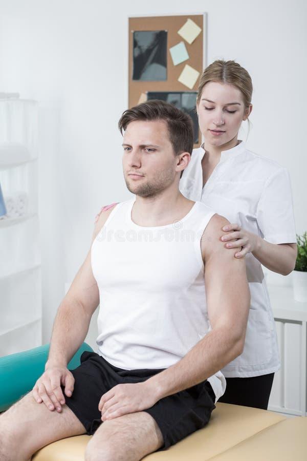 Terapeuta egzamininuje sportowego mężczyzna zdjęcia stock