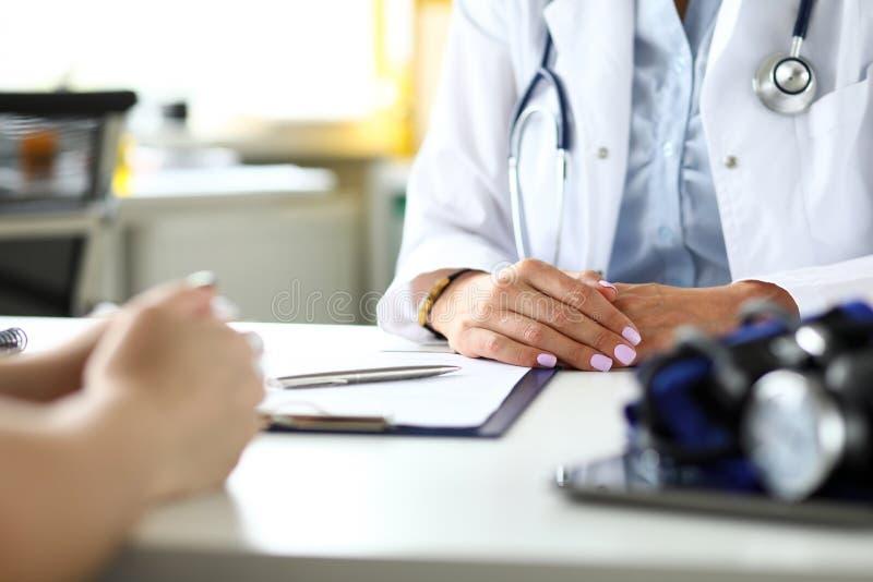Terapeuta en la clínica que recibe al visitante enfermo que discute denuncias de la salud imagen de archivo