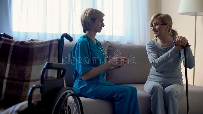 Terapeuta experimentado que mecanografía la tableta de datos médica, hablando con el paciente, salud foto de archivo libre de regalías