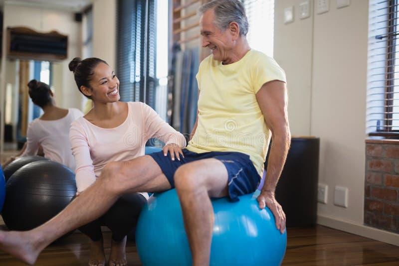 Terapeuta fêmea de sorriso que agacha-se pelo paciente masculino superior que senta-se na bola do exercício fotografia de stock