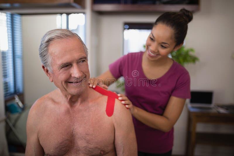 Terapeuta fêmea que aplica a fita terapêutica elástica no ombro do pati masculino superior descamisado de sorriso fotos de stock
