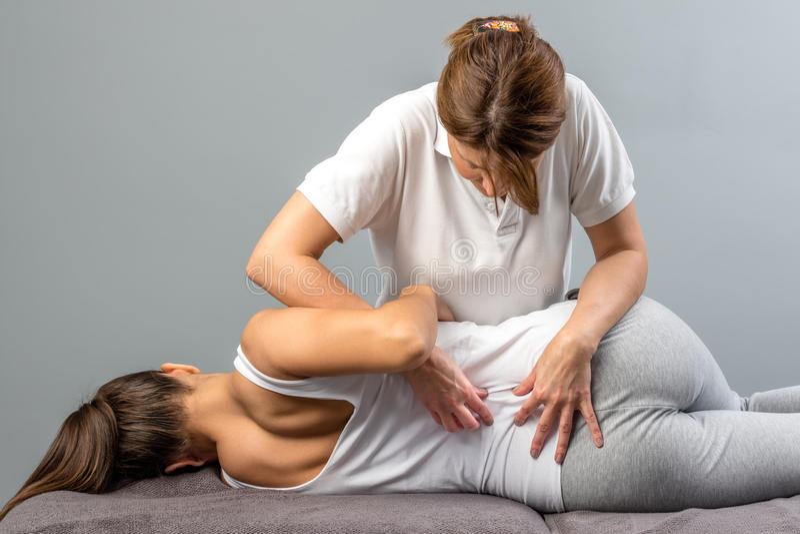 Terapeuta fêmea que faz o tratamento osteopathic da espinha no paciente foto de stock